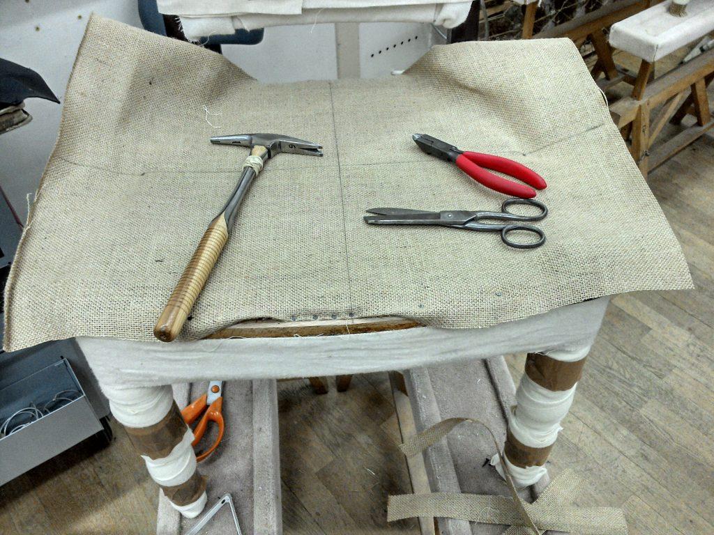 Stuhl, ungepolstert, Leinwand aufgenagelt, Werkzeuge liegen auf dem Stuhl,