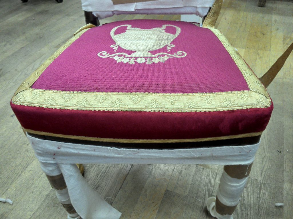fertig gepolsterter Sitz, roter Stoff in Boden und Spiegel wird von goldener Borte unterbrochn, den unteren Abschluss bildet ebenso eine goldene Borte
